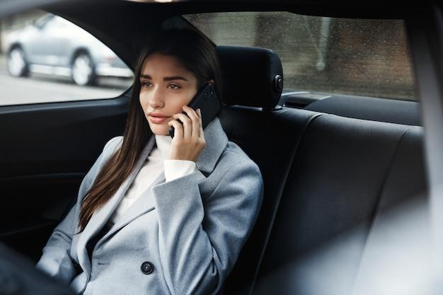 Zakenvrouw in haar auto zitten en praten over de telefoon