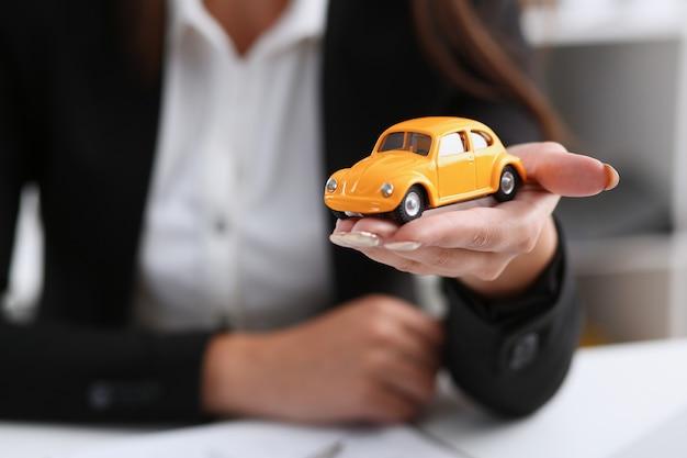 Zakenvrouw in het kantoor heeft een miniatuur speelgoed gele auto