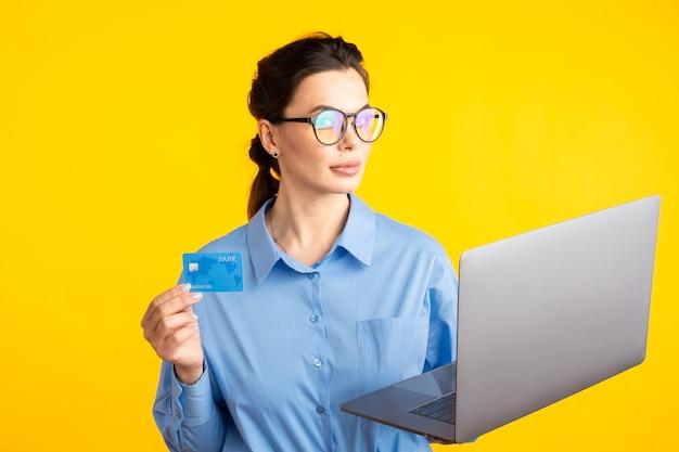 Zakenvrouw in het kantoor kleding en bril, waardoor online winkelen op geel