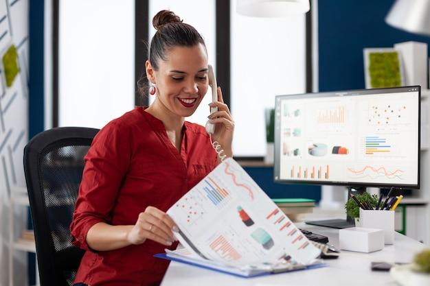 Zakenvrouw in het kantoor van het bedrijf die financiële statistieken controleert