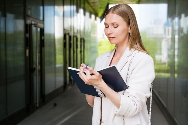Zakenvrouw in lichte jas staat en schrijft iets in de buurt van zakencentrum kaukasisch meisje schrijft...