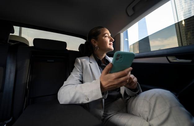 Zakenvrouw in mobiele personenauto op achterbank met smartphone