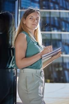 Zakenvrouw in mouwloos zomerpak maakt aantekening in dagboek