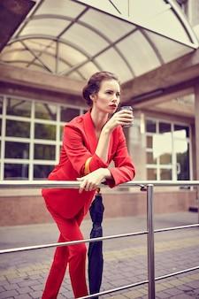 Zakenvrouw in rood kostuum met behulp van mobiele telefoon in de buurt van modern gebouw.