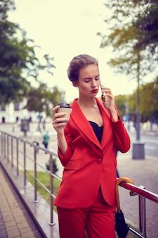 Zakenvrouw in rood kostuum met behulp van mobiele telefoon in de straat.