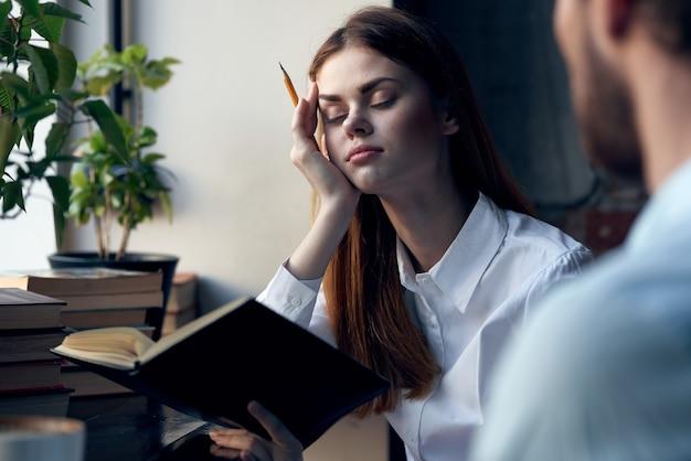 Zakenvrouw in shirt met boek in handen naast man kantoorwerk