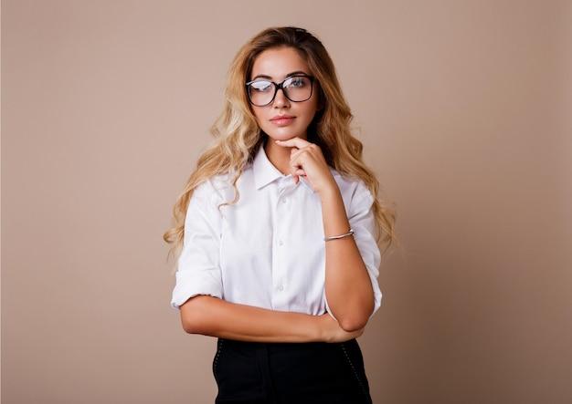 Zakenvrouw in stijlvolle brillen permanent over beige muur. blond golvende haren. witte blouse en zwarte broek.