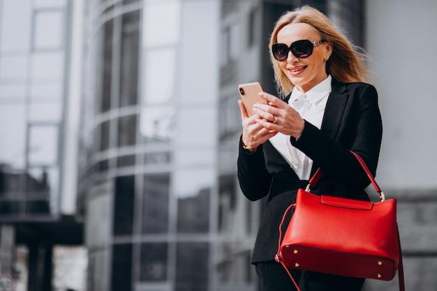 Zakenvrouw in stijlvolle outfit praten aan de telefoon bij het business center