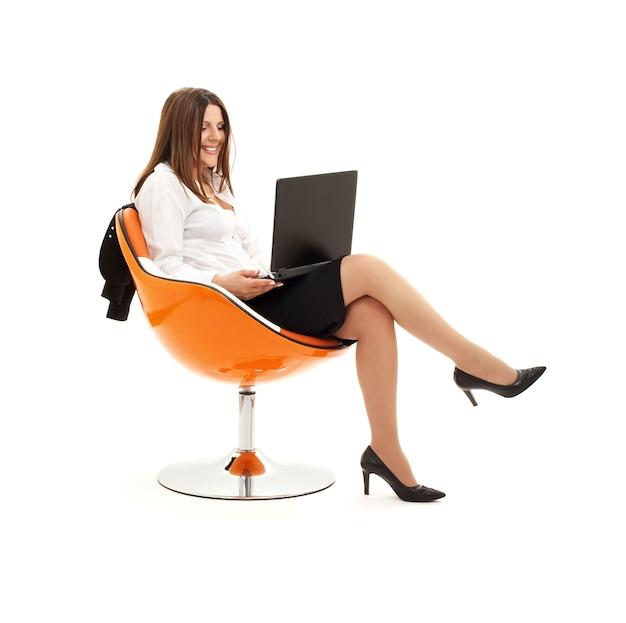 Zakenvrouw in stoel met laptop over wit