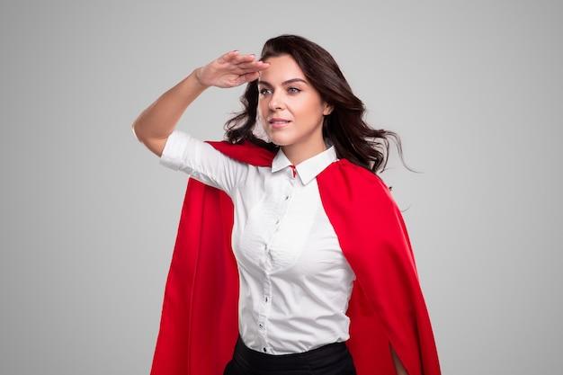 Zakenvrouw in superheld kostuum wegkijken