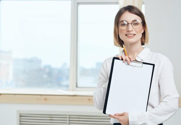 Zakenvrouw in wit overhemd en bril in de buurt van office manager window