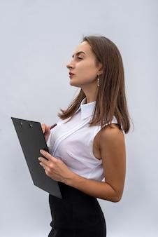 Zakenvrouw in wit overhemd met document op klembord, geïsoleerd op een witte achtergrond.
