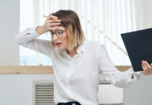 Zakenvrouw in wit overhemd met map in handen voor kantoorpapieren