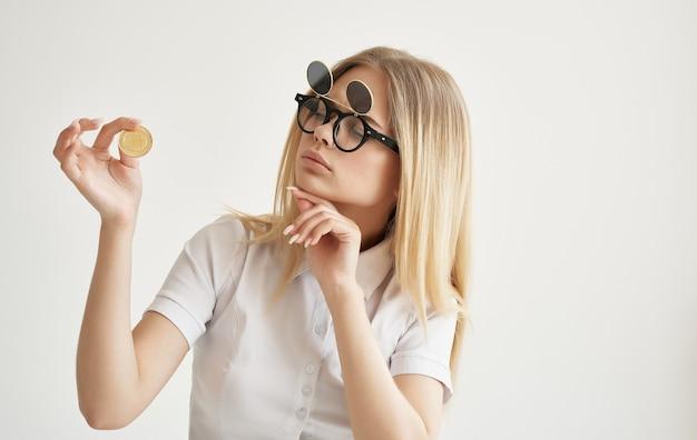 Zakenvrouw in zonnebril houdt bitcoin gouden cryptocurrency in handen internetfinanciën