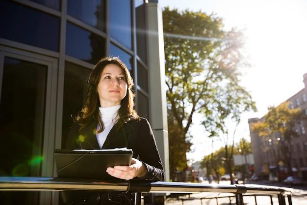 Zakenvrouw in zwart pak, zwarte map en papieren in de hand houden, staande voor kantoorgebouw en wegkijken