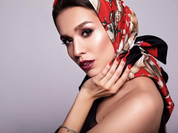 Zakenvrouw in zwarte jurk met avond make-up en kleurrijke lippen in rode sjaal