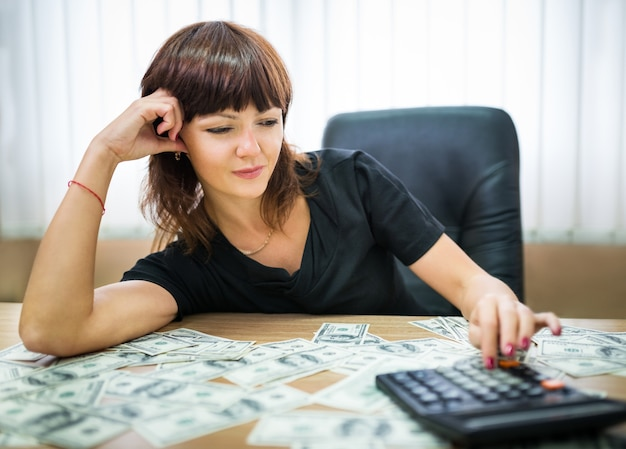 Zakenvrouw inkomen berekenen op een rekenmachine