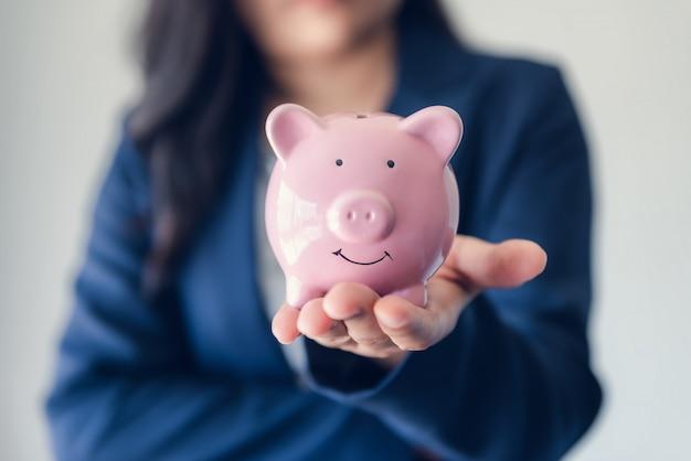 Zakenvrouw investeerder holding piggy bank voor geldbesparingen op haar handen.
