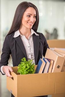 Zakenvrouw kartonnen doos met haar dingen te houden.