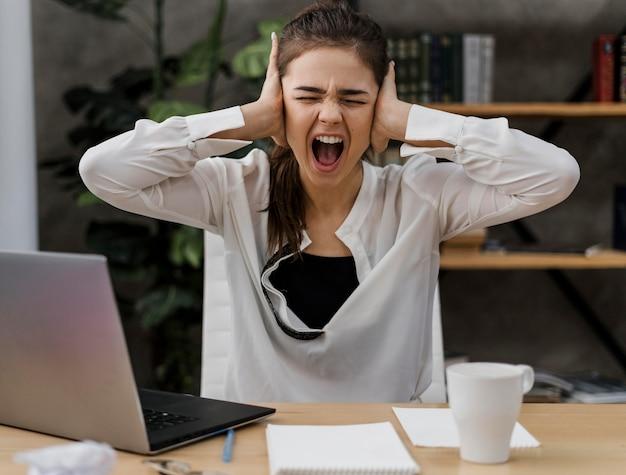 Zakenvrouw kijkt boos tijdens het werken vanuit huis