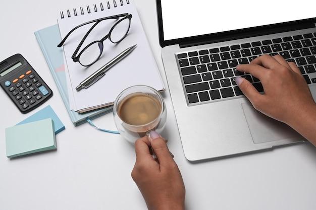 Zakenvrouw koffiekopje te houden en werken met laptopcomputer op wit bureau.
