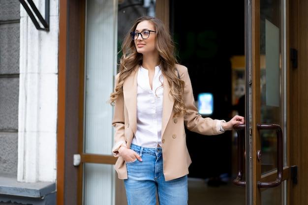 Zakenvrouw komen uit winkel deur buiten kaukasische vrouwelijke zakenman permanent in de buurt van winkel deuropening gekleed spijkerbroek jas bril houden deurklink