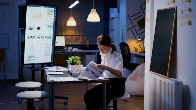 Zakenvrouw komt 's avonds laat in de vergaderruimte van het bedrijf en zit 's avonds laat aan het bureau en werkt aan marketingwinst die statistieken analyseert
