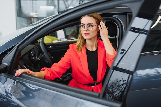 Zakenvrouw koopt een auto bij een autodealer.