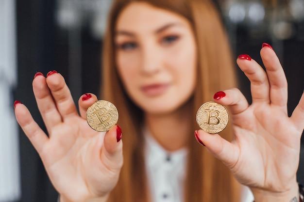 Zakenvrouw krijgt veel geld aantrekkelijke vrouw met rode nagels houdt twee bitcoins in handen