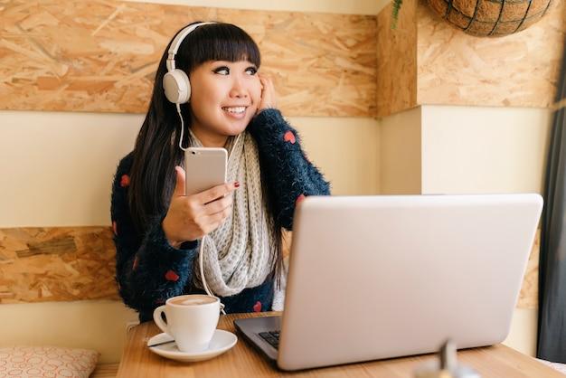 Zakenvrouw luisteren muziek in de coffee shop. bedrijfsconcept