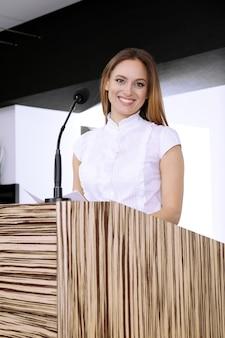 Zakenvrouw maakt toespraak op conferentieruimte