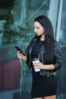 Zakenvrouw met behulp van digitale smartphone en koffie drinken in de buurt van het kantoorgebouw