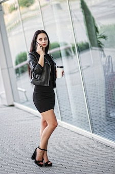 Zakenvrouw met behulp van digitale smartphone en koffie drinken in de buurt van naast kantoorgebouw.