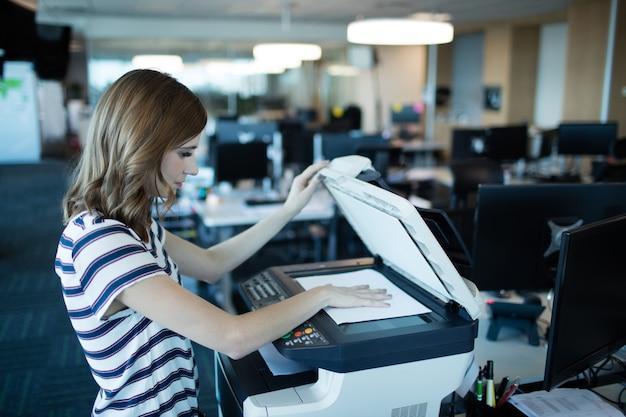 Zakenvrouw met behulp van kopieermachine in kantoor