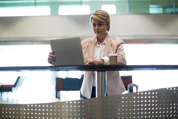 Zakenvrouw met behulp van laptop in wachtruimte