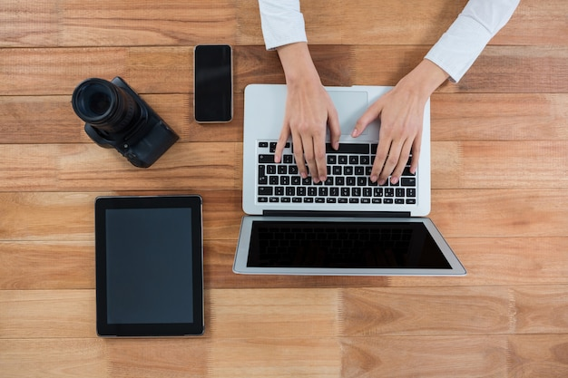 Zakenvrouw met behulp van laptop met camera, digitale tablet en mobiele telefoon