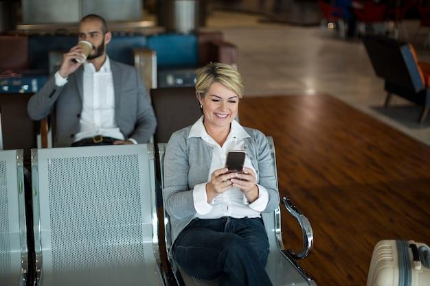 Zakenvrouw met behulp van mobiele telefoon in wachtruimte