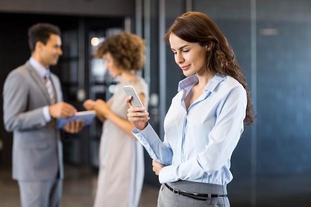 Zakenvrouw met behulp van mobiele telefoon met een collega's