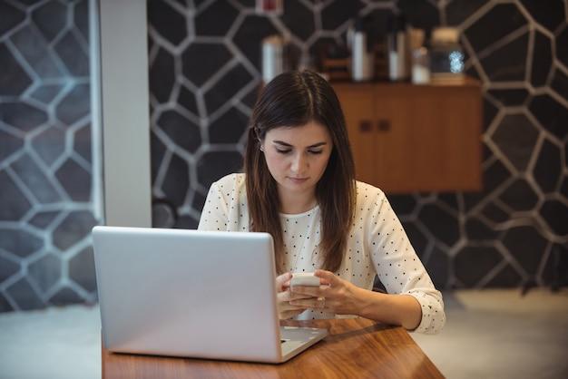 Zakenvrouw met behulp van mobiele telefoon met laptop op tafel