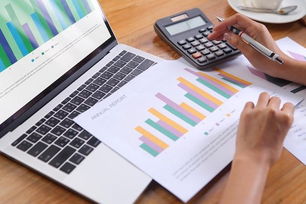 Zakenvrouw met behulp van rekenmachine berekenen jaarverslag met laptop en kantoorbenodigdheden op houten bureau