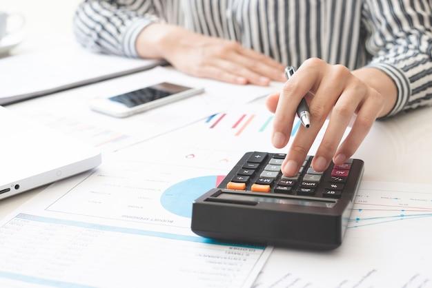 Zakenvrouw met behulp van rekenmachine en schrijven notitie maken met berekenen. belastingen en economische concepten.