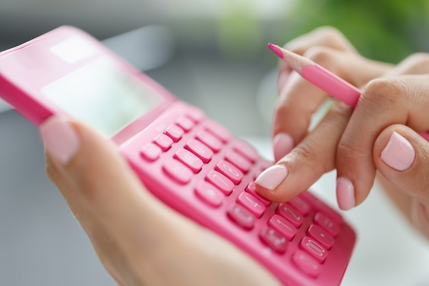Zakenvrouw met behulp van rekenmachine met pen in de hand financiële kosten budgettering berekenen
