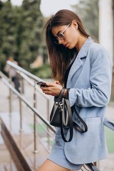 Zakenvrouw met behulp van telefoon buiten de straat