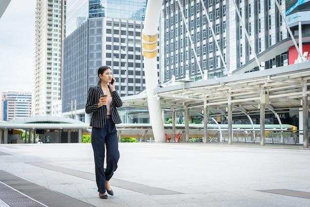 Zakenvrouw met behulp van telefoon met koffie in de hand lopen op de straat met kantoorgebouwen op de achtergrond