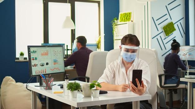Zakenvrouw met beschermingsmasker met smartphone met draadloze hoofdtelefoon voor videovergaderingen praten met een externe werknemer die in een nieuw normaal kantoor zit. collega's die werken met respect voor sociale afstand