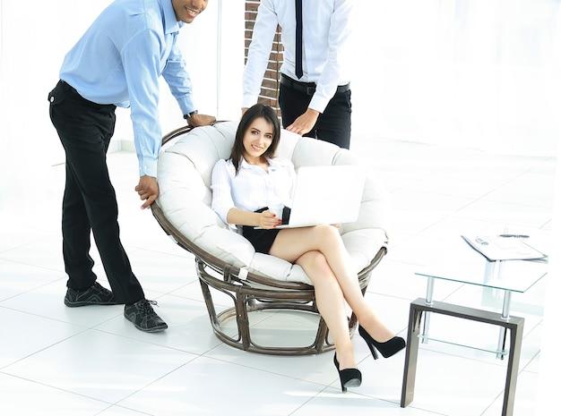 Zakenvrouw met collega's die werkproblemen bespreken, zittend in een comfortabele stoel