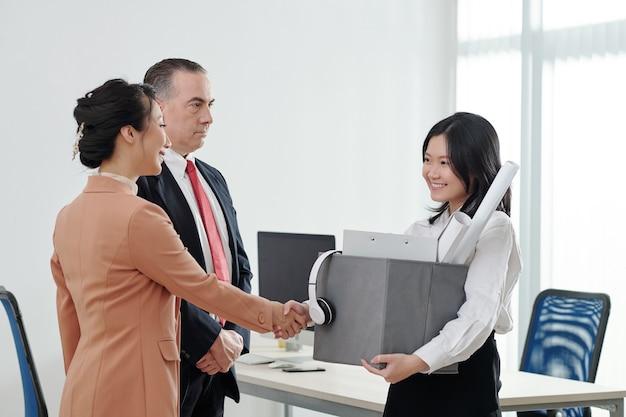 Zakenvrouw met doos met spullen die haar nieuwe collega's de hand schudt