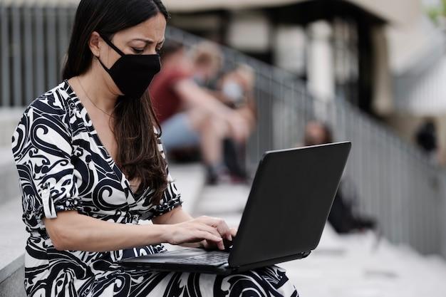 Zakenvrouw met een beschermend masker, die met haar laptop buiten werkt