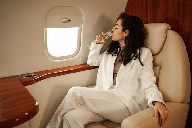 Zakenvrouw met een bril in een wit broekpak dat in een zakenvliegtuig vliegt en champagne drinkt