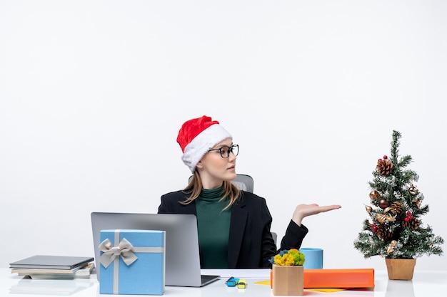 Zakenvrouw met een kerstman hoed zittend aan een tafel met een kerstboom en een cadeau